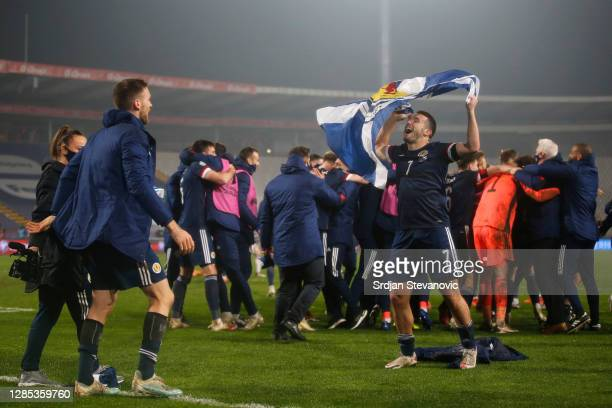 John McGinn of Scotland celebrates with a Scotland flag at the end of the match during the UEFA EURO 2020 Play-Off Final between Serbia and Scotland...