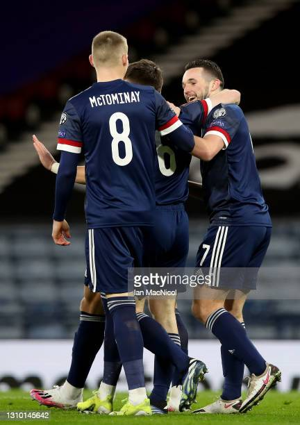 John McGinn of Scotland celebrates with team mate Kieran Tierney and Scott McTominay after scoring their side's first goal during the FIFA World Cup...