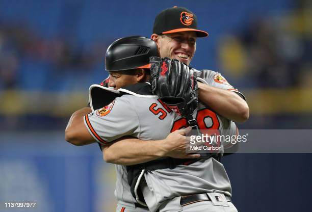 John Means of the Baltimore Orioles celebrates with Pedro Severino at the end of the 11th inning of a baseball game against the Tampa Bay Rays at...