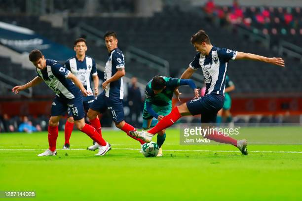 John Medina , Maximiliano Meza and Cesar Montes of Monterrey fight for the ball with Daniel Alvarez of Puebla during the repechage match between...