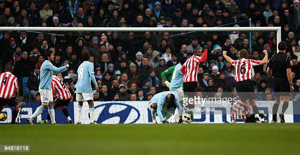 John Mensah of Sunderland scores his team's first goal as Micah Richards of Manchester City shows his dejection during the Barclays Premier League...