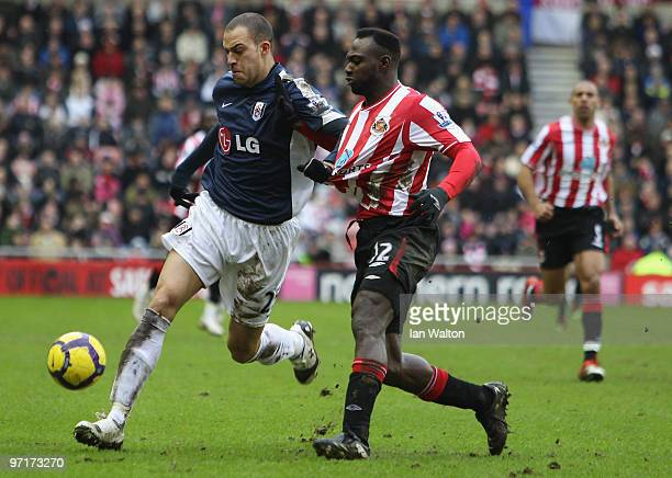 John Mensah of Sunderland tries to tackle Bobby Zamora of Fulham during the Barclays Premier League match between Sunderland and Fulham at Stadium of...