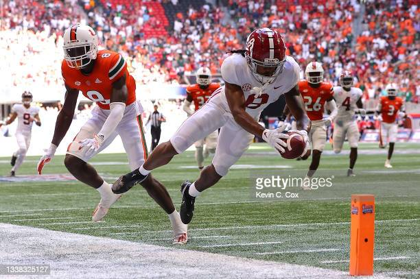 John Metchie III of the Alabama Crimson Tide dives for a touchdown against DJ Ivey of the Miami Hurricanes during the first half of the Chick-fil-A...