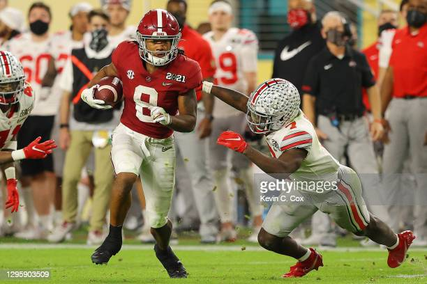 John Metchie III of the Alabama Crimson Tide rushes ahead of Sevyn Banks of the Ohio State Buckeyes during the fourth quarter of the College Football...