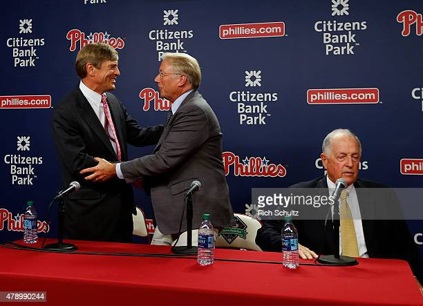 John Middletown left part owner of Philadelphia Phillies shakes hands with Andy MacPhail center as Pat Gillick right looks on after a press...