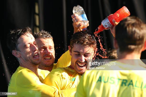 John Millman captain Lleyton Hewitt of Australia and Jordan Thompson spray Gatorade as they celebrate after winning the Davis Cup Qualifiers between...