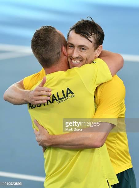 John Millman of Australia celebrates winning the match hugs Lleyton Hewitt captain of Australia during the Davis Cup Qualifier singles match between...