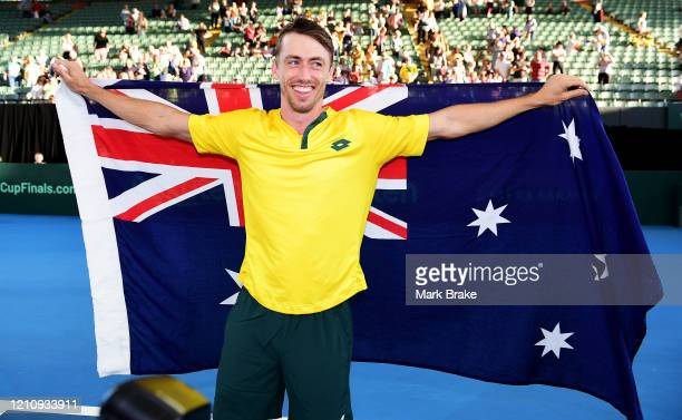 John Millman of Australia celebrates with the Australian flag after the Davis Cup Qualifier singles match between John Millman of Australia and...