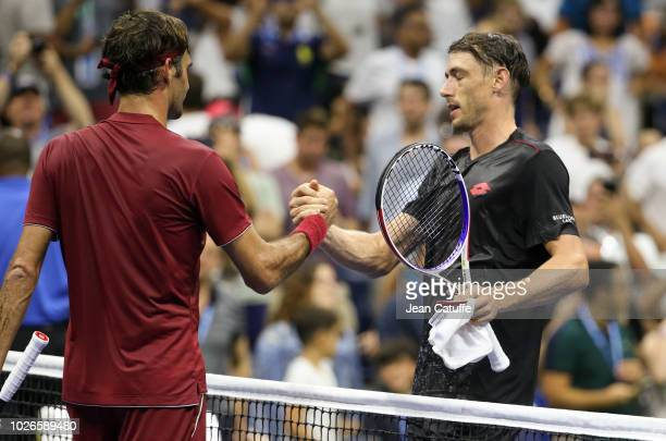 John Millman of Australia greets Roger Federer of Switzerland at the net after beating him during day 8 of the 2018 US Open at Arthur Ashe Stadium of...