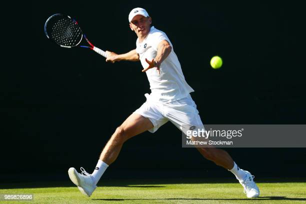 John Millman of Australia returns against Stefano Travaglia of Italy during their Men's Singles first round match on day one of the Wimbledon Lawn...