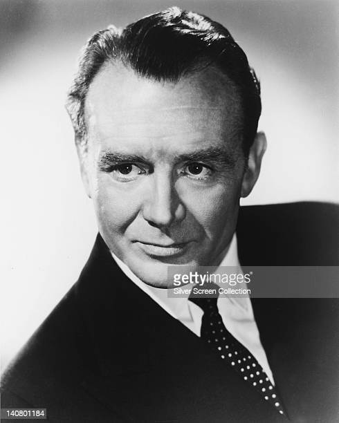 John Mills British actor wearing a black jacket over a white shirt with a black tie with white polka dots in a studio portrait against a light...