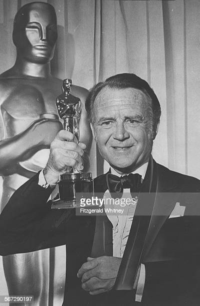 John Mills holds his prize after being named best supporting actor for his performance in Ryan's Daughter Mill's arm is in a sling as a result of an...
