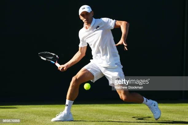 John Milman of Australia returns against Stefano Travaglia of Italy during their Men's Singles first round match on day one of the Wimbledon Lawn...