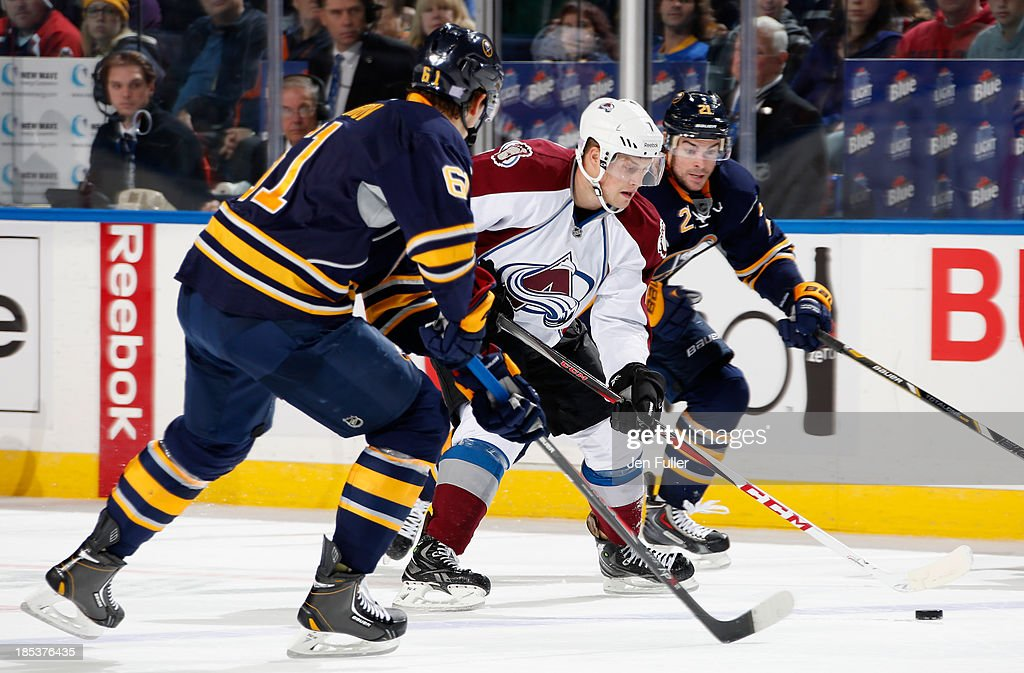 John Mitchell #7 of the Colorado Avalanche carries the puck between Drew Stafford #21 and Nikita Zadorov #61 of the Buffalo Sabres at First Niagara Center on October 19, 2013 in Buffalo, New York. Zadorov skates in his first NHL game. Colorado defeated Buffalo 4-2.