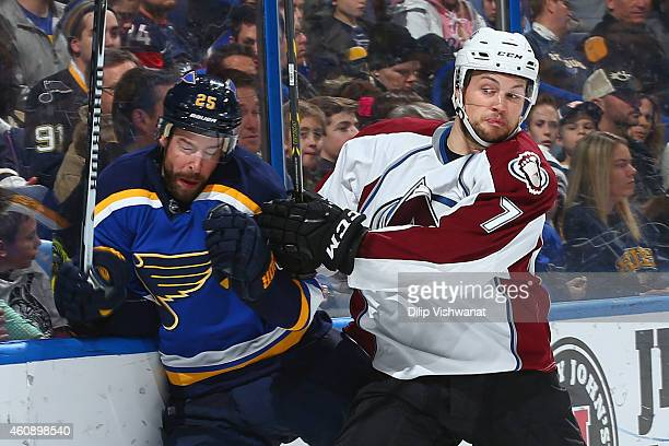 John Mitchell of the Colorado Avalanche checks Chris Butler of the St Louis Blues into the boards at the Scottrade Center on December 29 2014 in St...