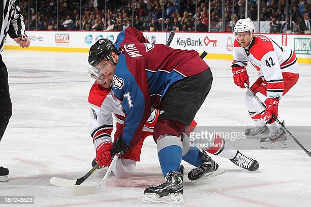 John Mitchell of the Colorado Avalanche faces off against Elias Lindholm of the Carolina Hurricanes at the Pepsi Center on October 25, 2013 in...