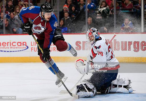 John Mitchell of the Colorado Avalanche leaps to avoid a shot by his teammate as goalie Braden Holtby of the Washington Capitals defends the goal at...