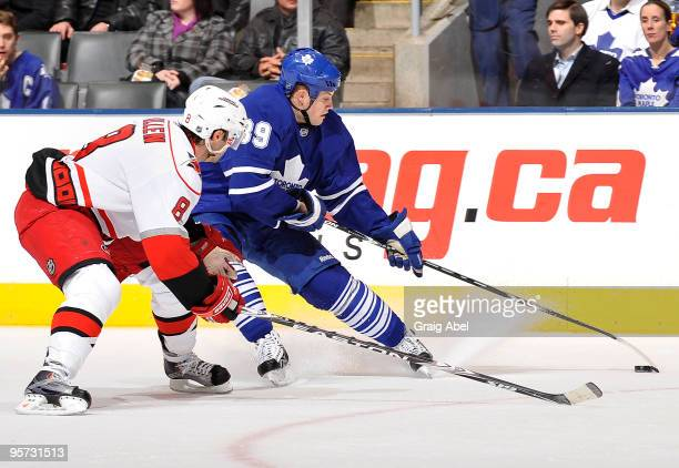 John Mitchell of the Toronto Maple Leafs battles for the puck with Matt Cullen of the Carolina Hurricanes during game action January 12 2010 at the...
