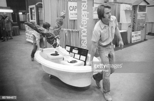 John Molzer front right and Jeff Deitchel of Marquis Marble Co bring in a bathtub for their display Home furnishings and decorations will be a...