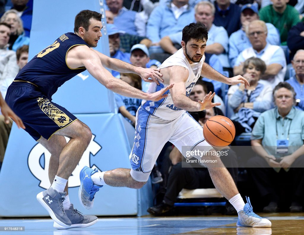 John Mooney #33 of the Notre Dame Fighting Irish and Luke Maye #32 of the North Carolina Tar Heels chase down a loose ball during their game at the Dean Smith Center on February 12, 2018 in Chapel Hill, North Carolina.