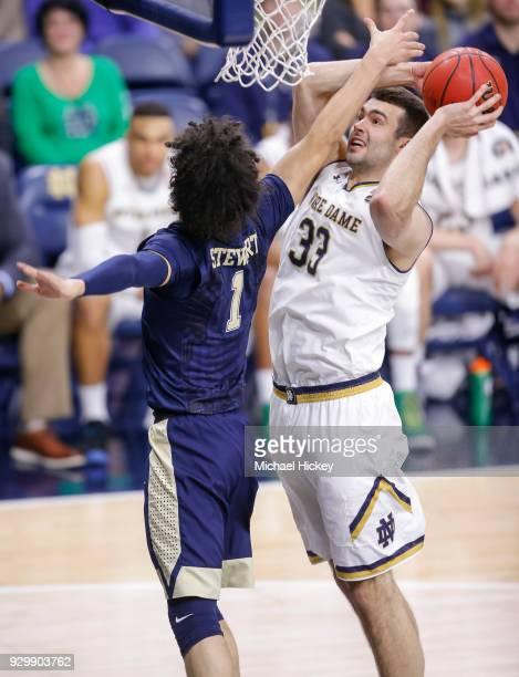 John Mooney of the Notre Dame Fighting Irish shoots the ball against Parker Stewart of the Pittsburgh Panthers at Purcell Pavilion on February 28...