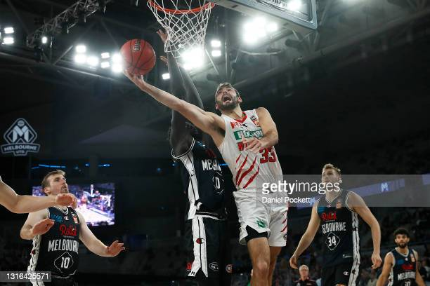 John Mooney of the Wildcats drives to the basket under pressure from Jo Lual Acuil of United during the round 16 NBL match between Melbourne United...
