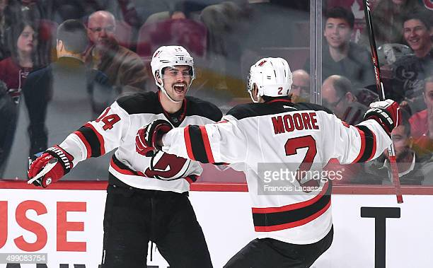 John Moore and Adam Henrique of the New Jersey Devils celebrate after defeating the the Montreal Canadiens in the NHL game at the Bell Centre on...