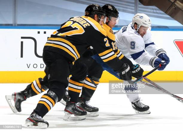 John Moore and Charlie Coyle of the Boston Bruins chase Tyler Johnson of the Tampa Bay Lightning during the first period of Game Three of the Eastern...