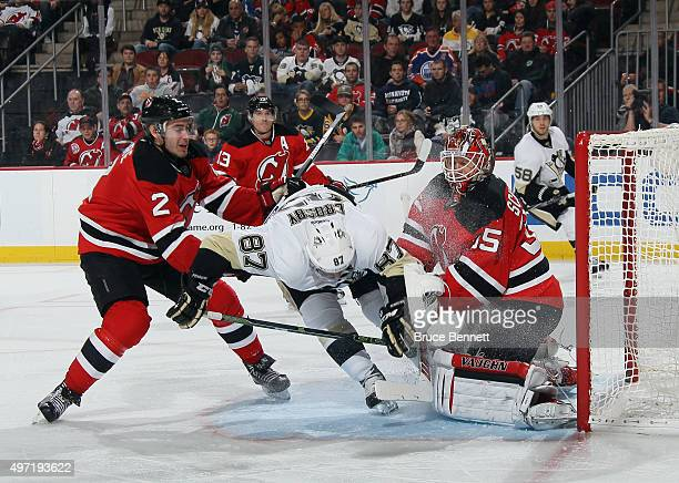 John Moore and Cory Schneider of the New Jersey Devils defend against Sidney Crosby of the Pittsburgh Penguins during the third period at the...