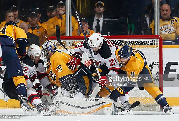 John Moore and Kyle Palmieri of the New Jersey Devils crash the net against Pekka Rinne and Ryan Ellis of the Nashville Predators during an NHL game...
