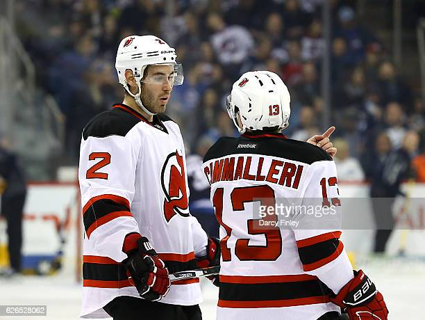 John Moore and Michael Cammalleri of the New Jersey Devils discuss strategy during a first period stoppage in play against the Winnipeg Jets at the...