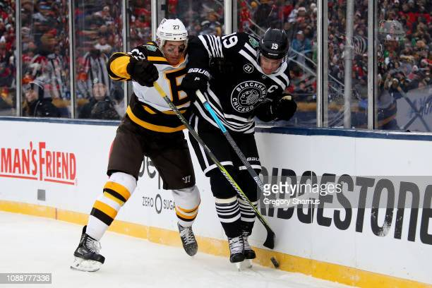 John Moore of the Boston Bruins and Jonathan Toews of the Chicago Blackhawks battle for the puck in the third period during the 2019 Bridgestone NHL...