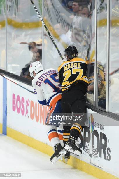 John Moore of the Boston Bruins collides with Cal Clutterbuck of the New York Islanders at the TD Garden on November 29 2018 in Boston Massachusetts
