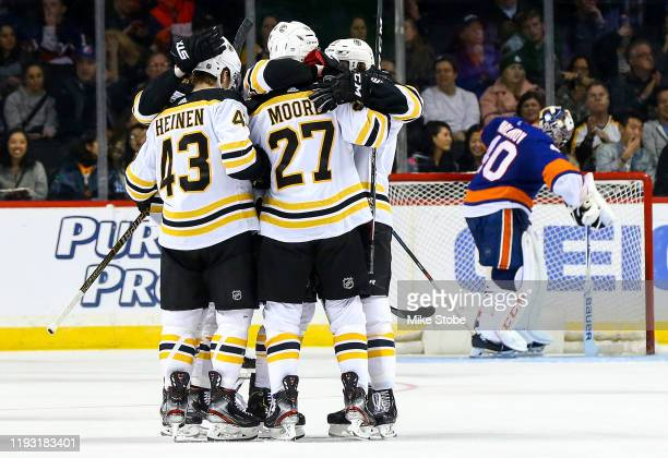 John Moore of the Boston Bruins is congratulated by his teammates after scoring a third period goal past Semyon Varlamov of the New York Islanders at...