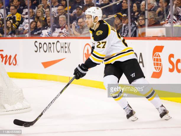 John Moore of the Boston Bruins plays the puck around the net during first period action against the Winnipeg Jets at the Bell MTS Place on March 14...