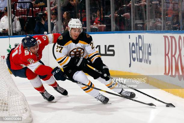John Moore of the Boston Bruins skates with the puck against Juho Lammikko of the Panthers at the BB&T Center on December 4, 2018 in Sunrise, Florida.