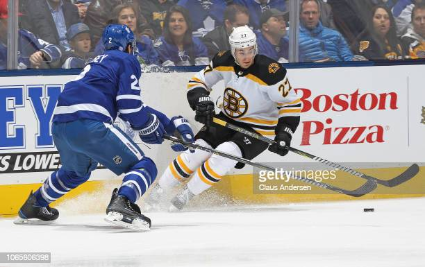 John Moore of the Boston Bruins skates with the puck against Ron Hainsey of the Toronto Maple Leafs during an NHL game at Scotiabank Arena on...