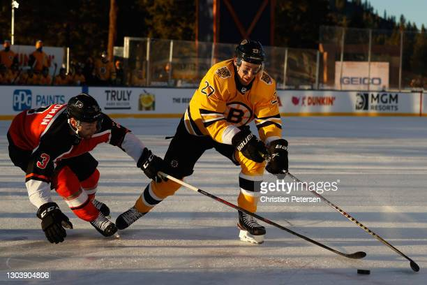 John Moore of the Boston Bruins skates with the puck past Mark Friedman of the Philadelphia Flyers during the 'NHL Outdoors At Lake Tahoe' at the...