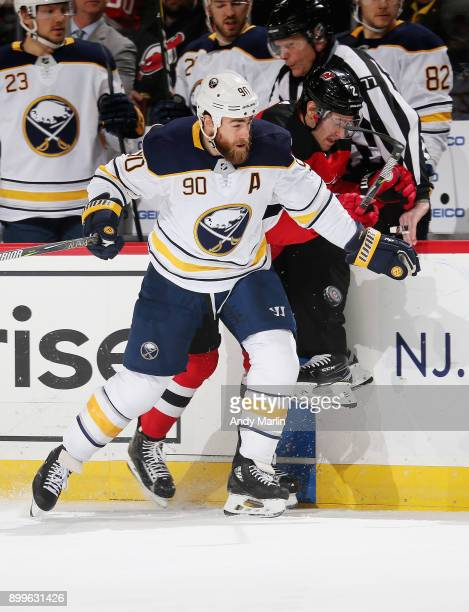 John Moore of the New Jersey Devils and Ryan O'Reilly of the Buffalo Sabres come together at the boards during the game at Prudential Center on...