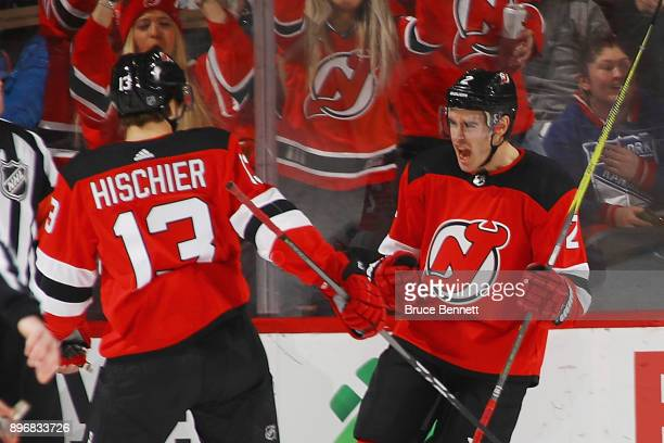 John Moore of the New Jersey Devils celebrates his goal at 722 of the first period against the New York Rangers and is joined by Nico Hischier at the...
