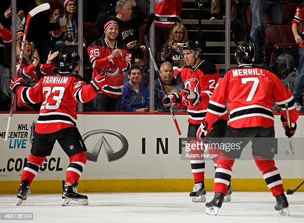 John Moore of the New Jersey Devils celebrates with Bobby Farnham and Jon Merrill after scoring a goal against the New York Islanders during the...
