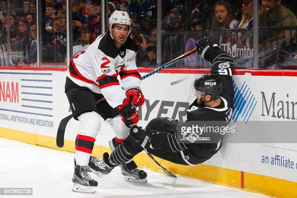 John Moore of the New Jersey Devils checks Andrew Ladd of the New York Islanders at the Barclays Center on February 19 2017 in Brooklyn borough of...
