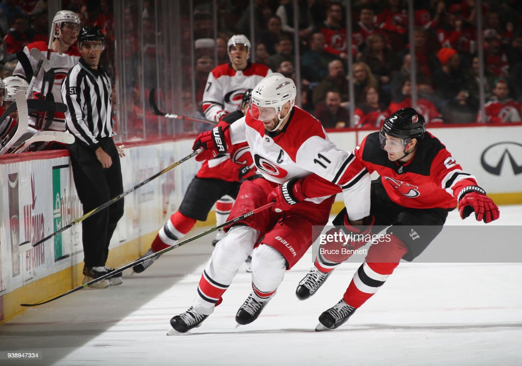 John Moore #2 of the New Jersey Devils checks Jordan Staal #11 of the Carolina Hurricanes during the third period at the Prudential Center on March 27, 2018 in Newark, New Jersey. The Devils defeated the Hurricanes 4-3.