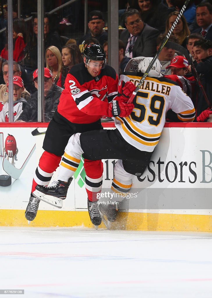 John Moore #2 of the New Jersey Devils checks Tim Schaller #59 of the Boston Bruins at the boards during the game at Prudential Center on November 22, 2017 in Newark, New Jersey.