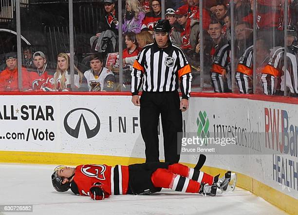 John Moore of the New Jersey Devils is injured on a hit into the boards by Tom Wilson of the Washington Capitals during the first period at the...