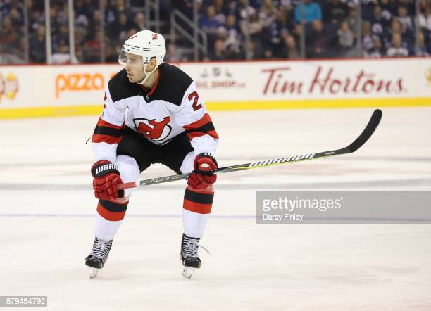 John Moore of the New Jersey Devils keeps an eye on the play during third period action against the Winnipeg Jets at the Bell MTS Place on November...
