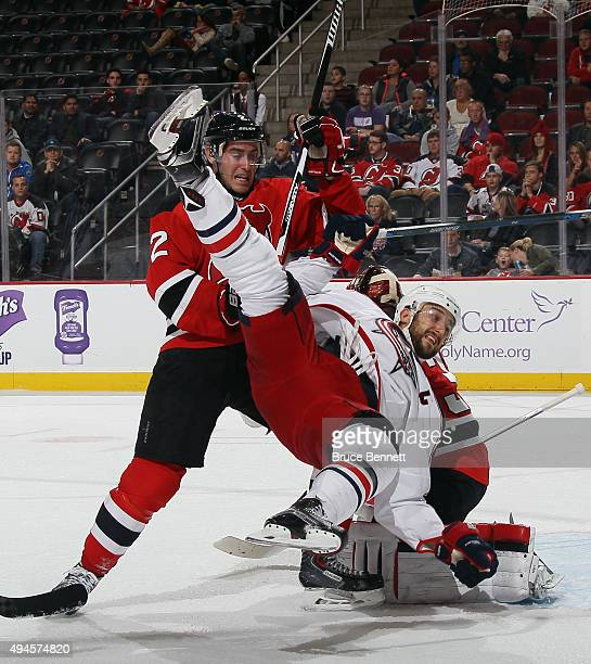 John Moore of the New Jersey Devils takes a penalty for interference on Nick Foligno of the Columbus Blue Jackets during the third period at the...