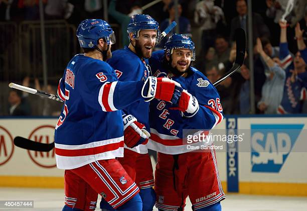 John Moore of the New York Rangers celebrates a goal by Benoit Pouliot with teammates Mats Zuccarello and Dan Girardi in the first period in the...