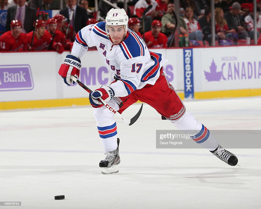 John Moore #17 of the New York Rangers chases a loose puck against the Detroit Red Wings during an NHL game at Joe Louis Arena on October 26, 2013 in Detroit, Michigan. The Rangers win in O
