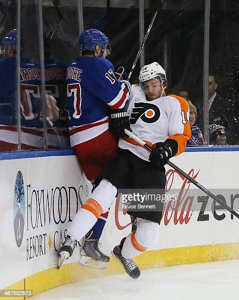 John Moore of the New York Rangers is hit into the boards by Sean Couturier of the Philadelphia Flyers during the first period in Game Seven of the...
